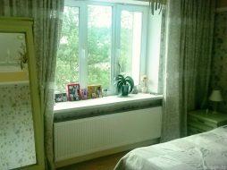 Стальной радиатор в спальне у кровати